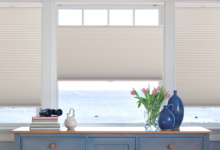 Window shades in room overlooking ocean