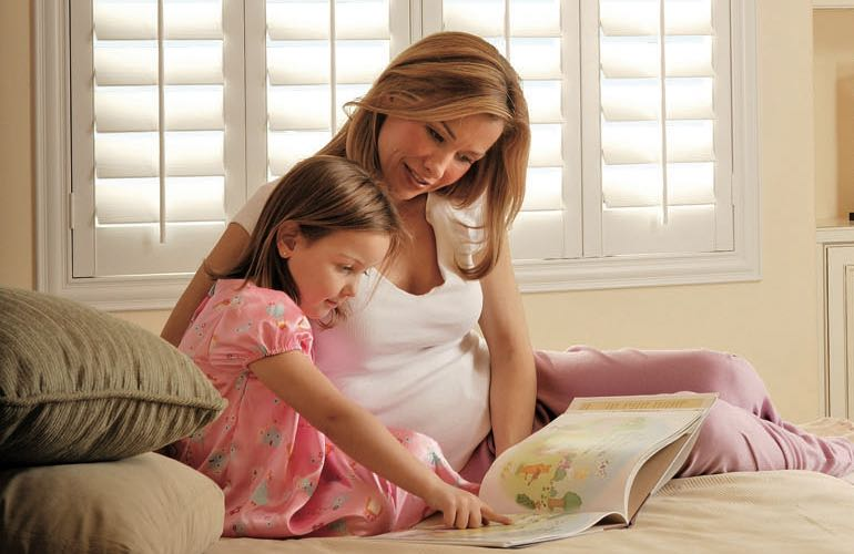 Parent and girl reading on bed with shuttered windows.