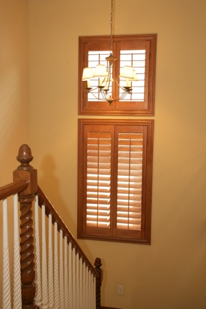 Wooden plantation shutters in tan staircase.