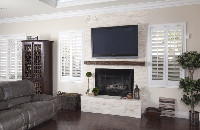 White plantation shutters in a Phoenix living room with solid hardwood floors.