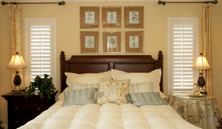 Beige bedroom with white plantation shutters covering windows in Phoenix